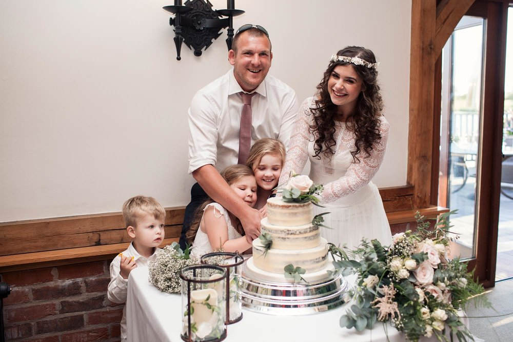 bride and groom family cutting the wedding cake at the wedding cheshire leeds 2018