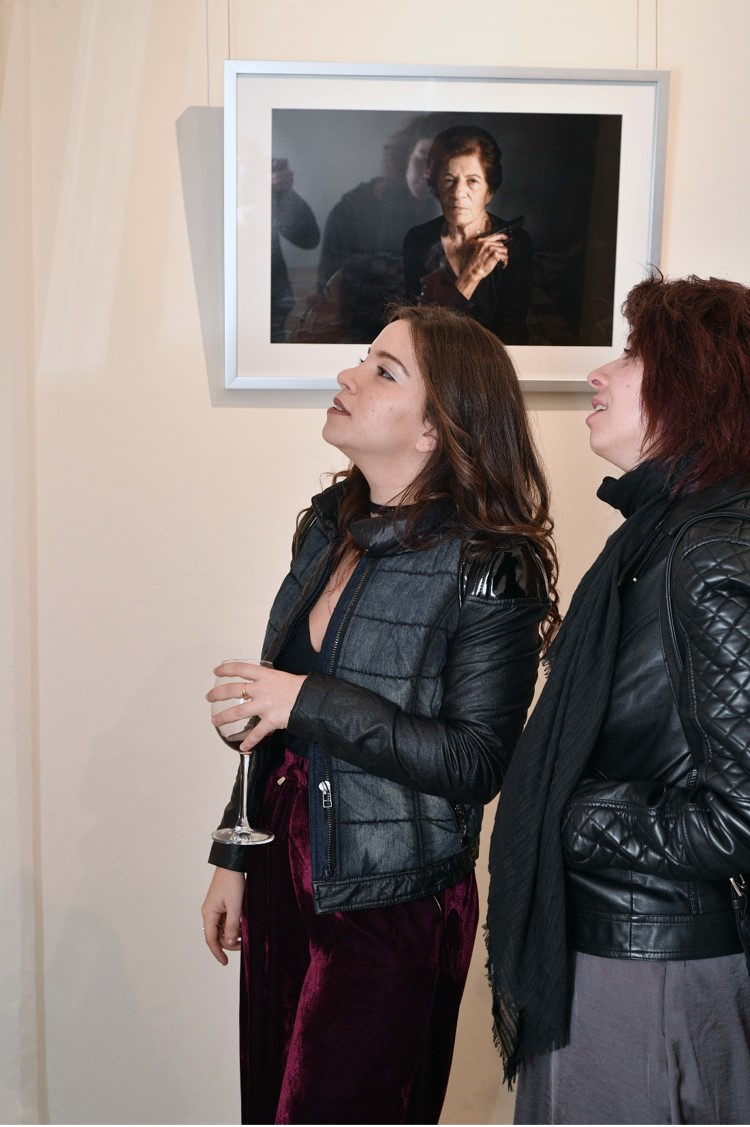 "Carmen Yahchoucky (on the left) next to her photography ""Victoria"""