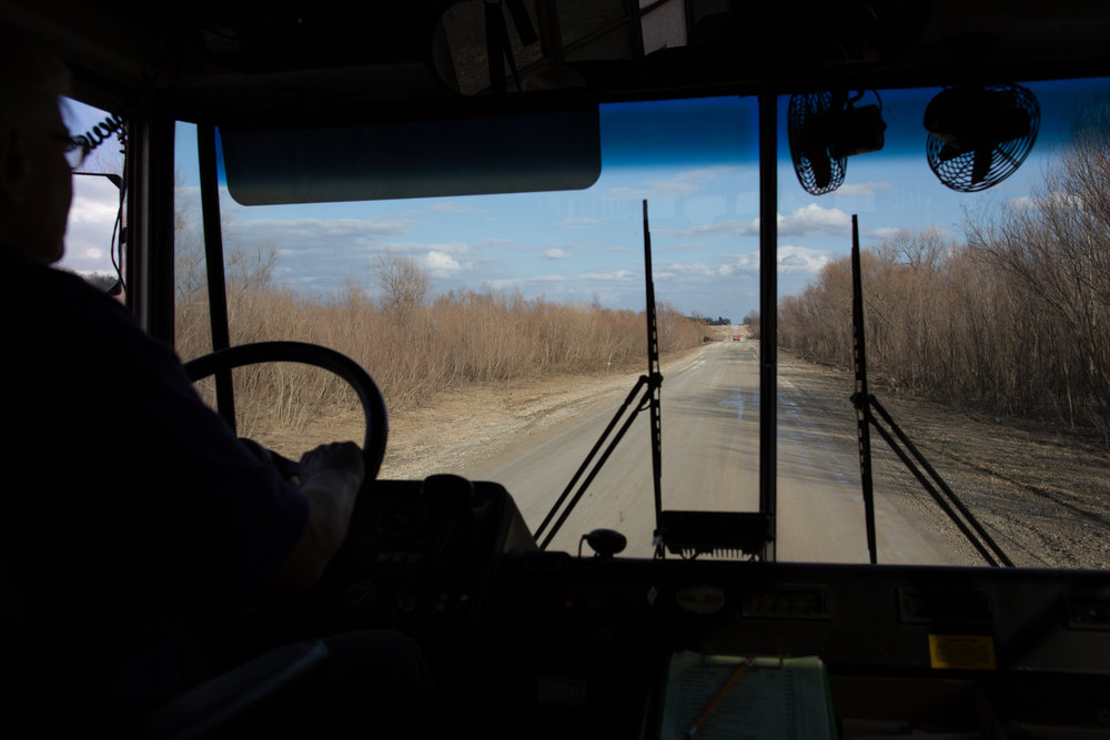 A school bus driver navigates a muddy, unpaved road in Solon, Iowa on Tuesday, March 8, 2016.