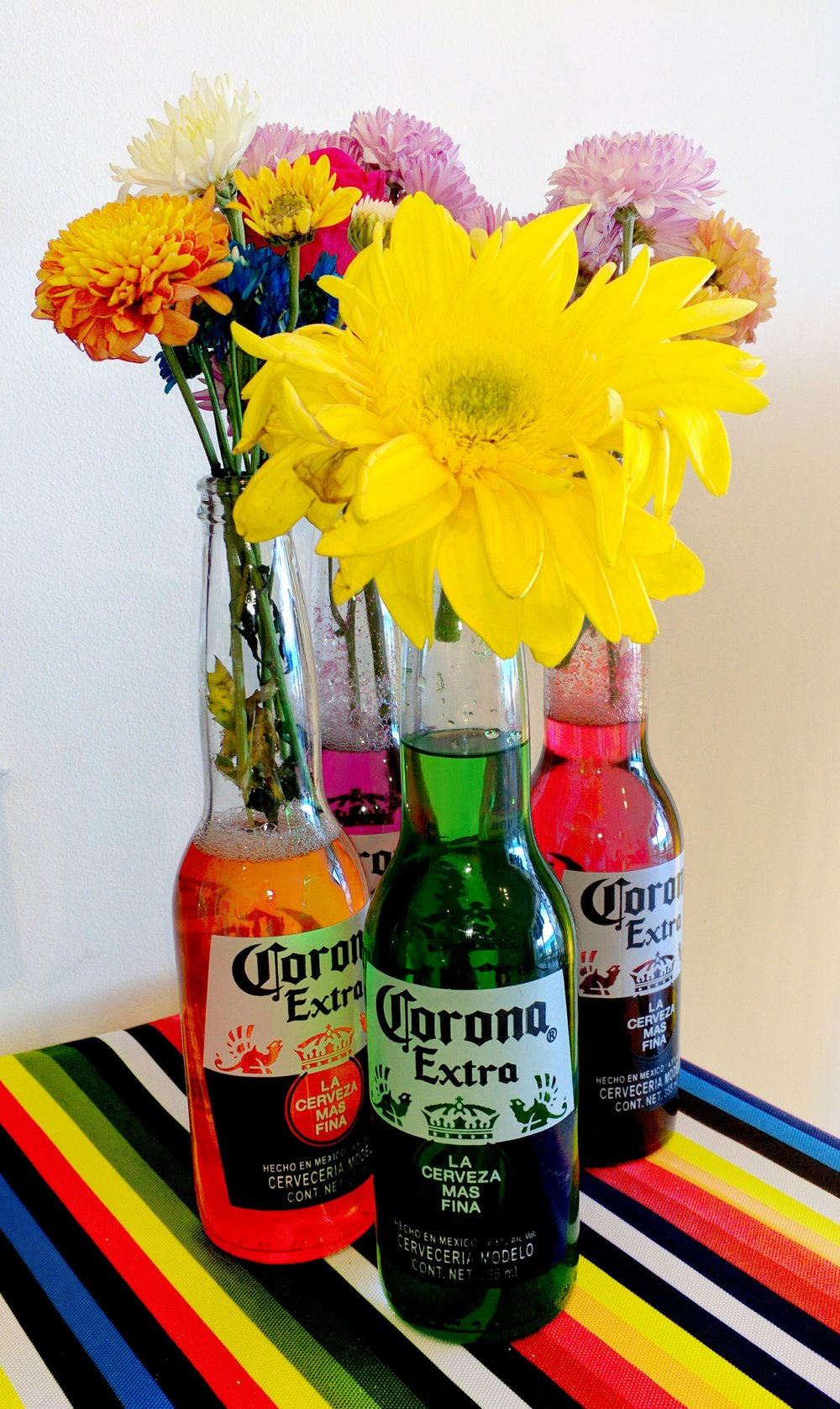 Fill up empty Corona bottles with food coloring! Make sure you bring the food coloring with you. They did not have this at the store so we did it with jello instead!