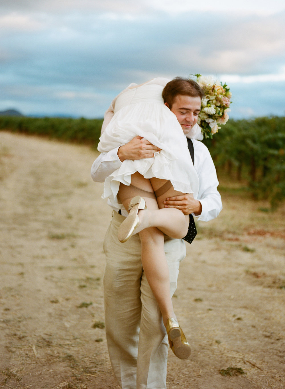 36-4-groom-carries-bride-shoulder.jpg
