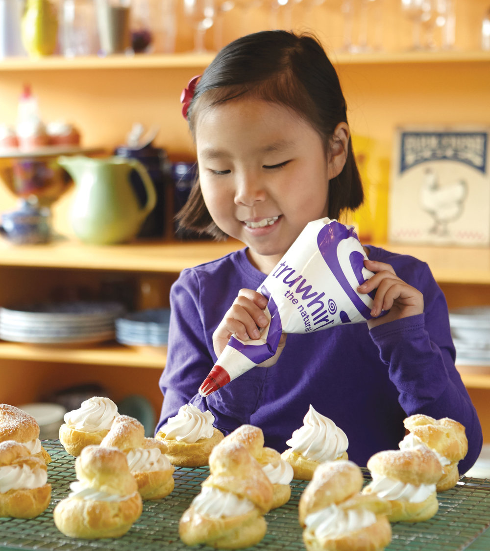 Kid dispensing truwhip on pastry creative advertising