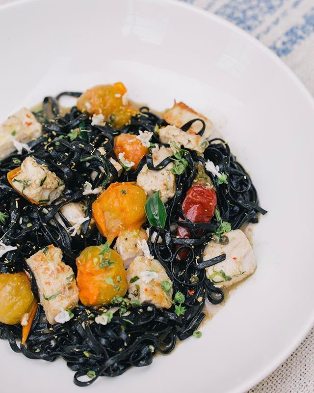 "Squid ink tagliatelle: confit swordfish, sungolds, Calabrian chilies, capers & flowering basil #eatitalian ""it's something you'd eat if you were hanging out on the Amalfi coast drinking a crisp glass of white wearing a fedora"" - @kjacovino"