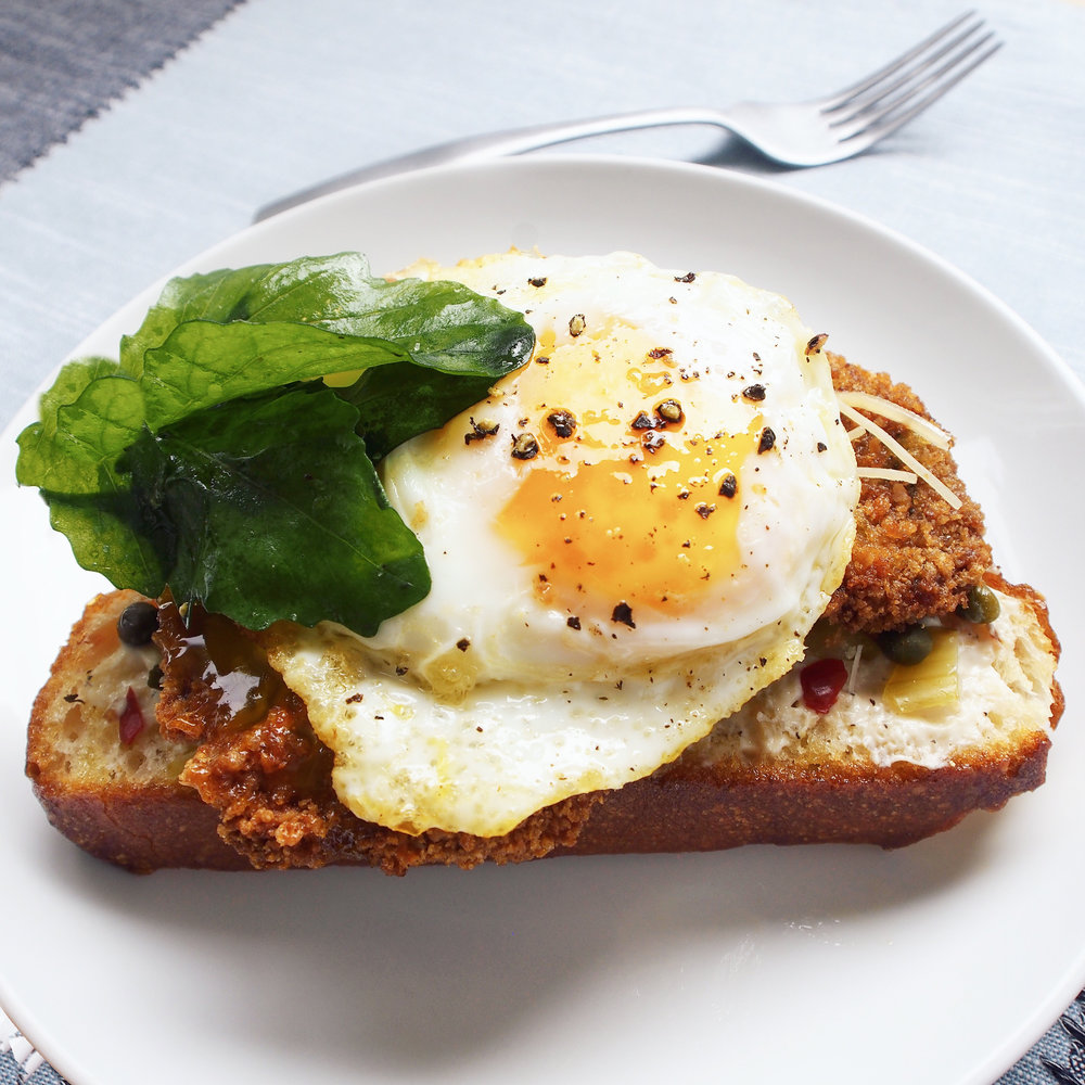 This crispy pork cutlet and fried egg sandwich is served open-faced on ciabatta bread