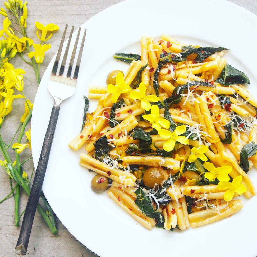 Kale Pasta with Kale Flowers in a Garlic-Infused Tomato Sauce! Such a tasty kale pasta recipe to finish off your kale when it goes to seed! I love using up the edible flowers in my garden and this recipe is one of the best for them!