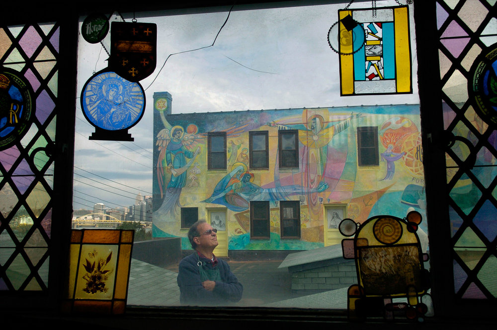 Nick Parrendo and his mural on a wall of Hunt Stained Glass Studios.