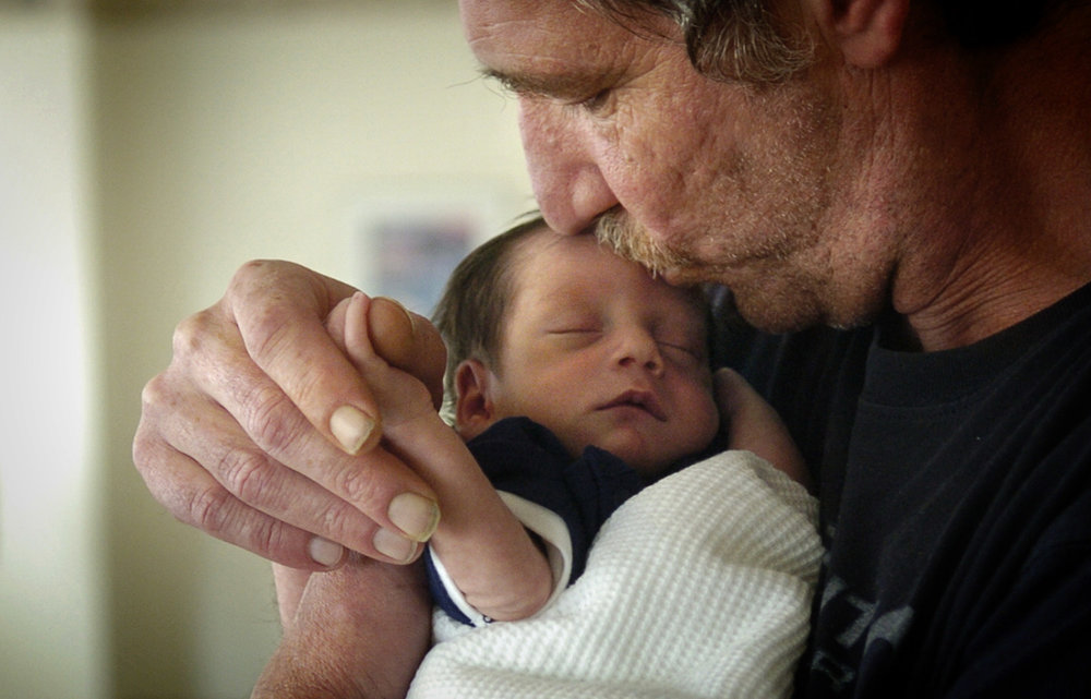 Jim Lowers holds grandson Jayden Antill in an intensive care unit.