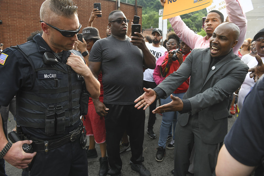 Leonard Hammonds II points out that a police officer has his hand on a weapon during a rally to protest police shooting of young black men.