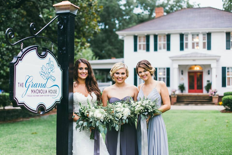 bride with the grand magnolia sign.jpg
