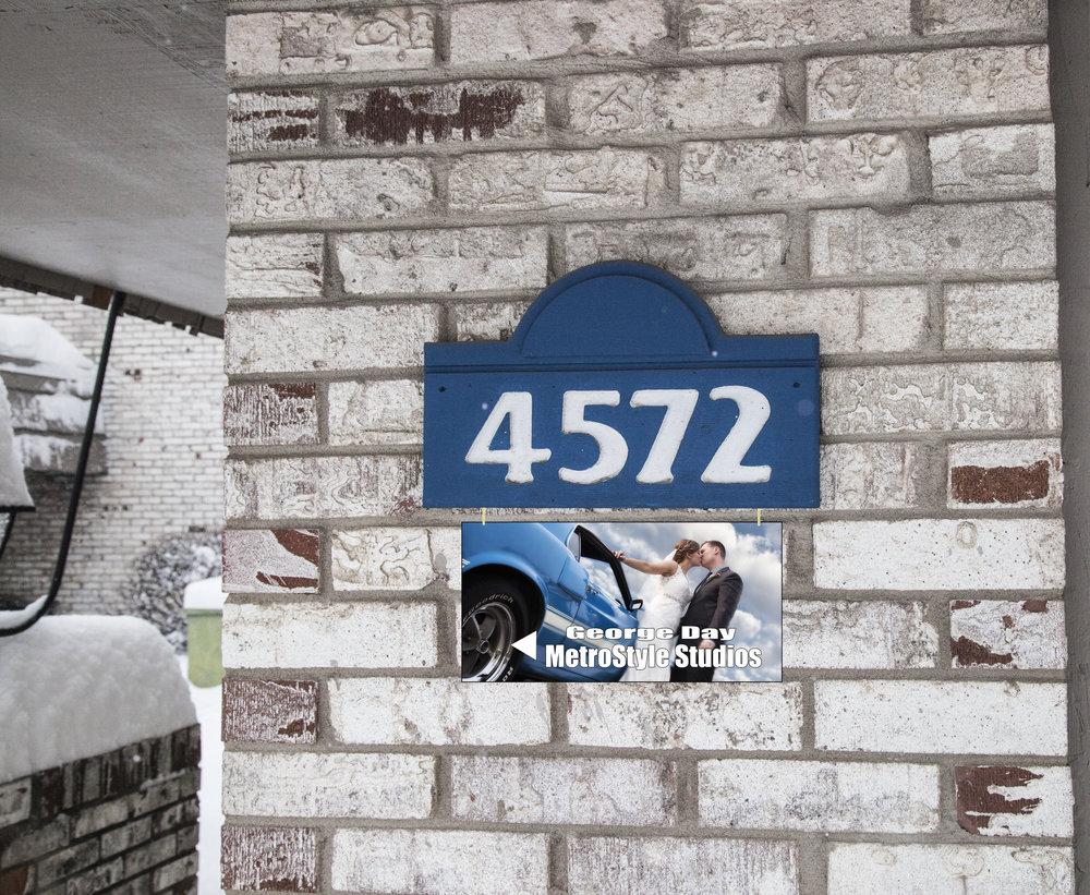 Blue METAL sign hanging on front of TLN building.jpg