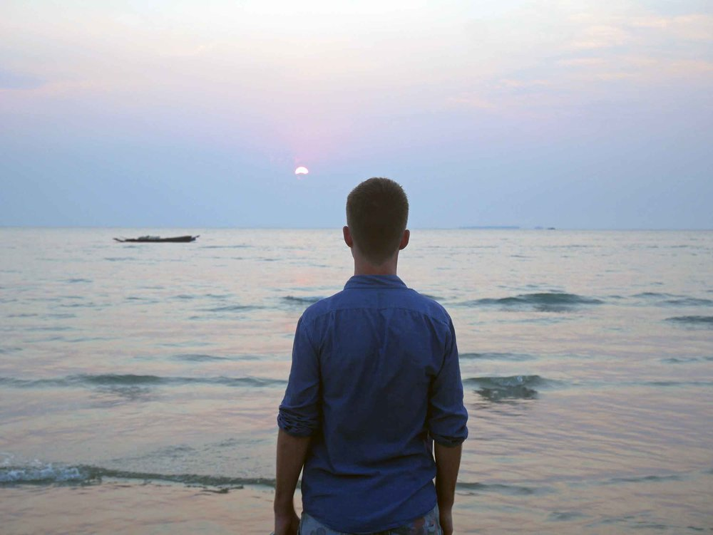 Trey taking in the breathtaking sunset of Ngwesaung, where the sun disappears before it hits the horizon.