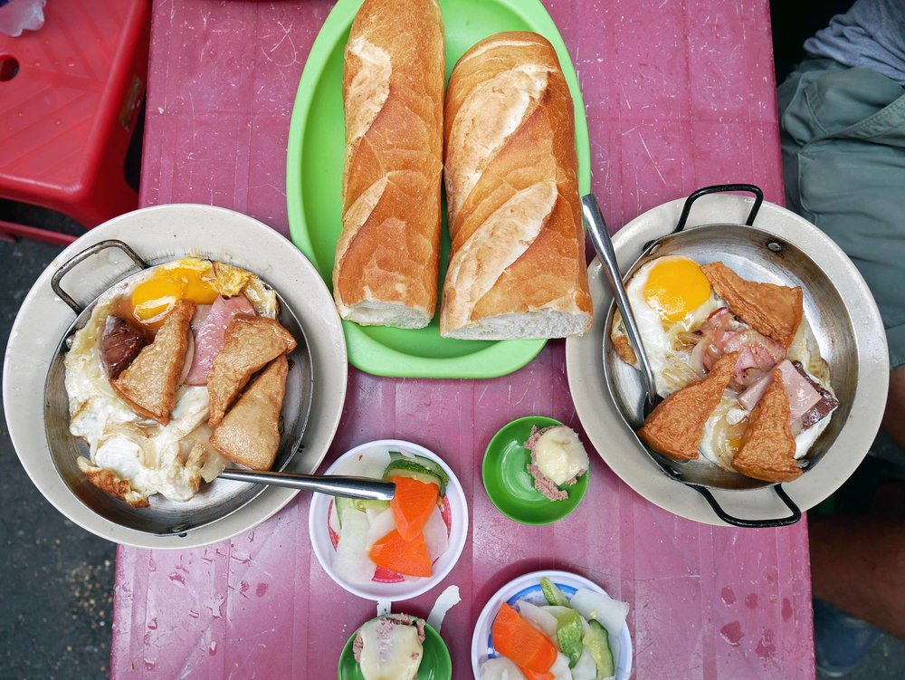 Served with flaky baguettes and pickled vegetables, the still sizzling eggs were topped with pork, onions and tofu.