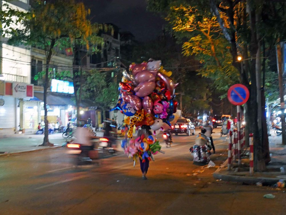 Like in Saigon, anything can be carried on or sold from a motorbike.... balloons!