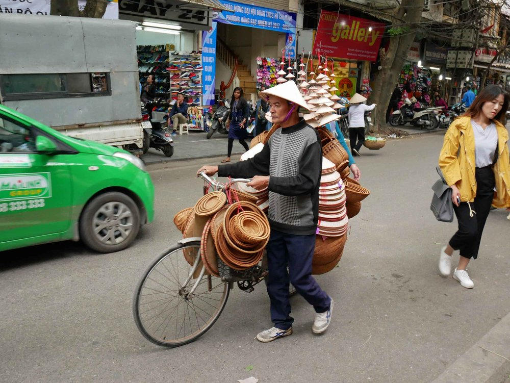 The bike is so overloaded with baskets and hats that he had to sell some before hopping on!