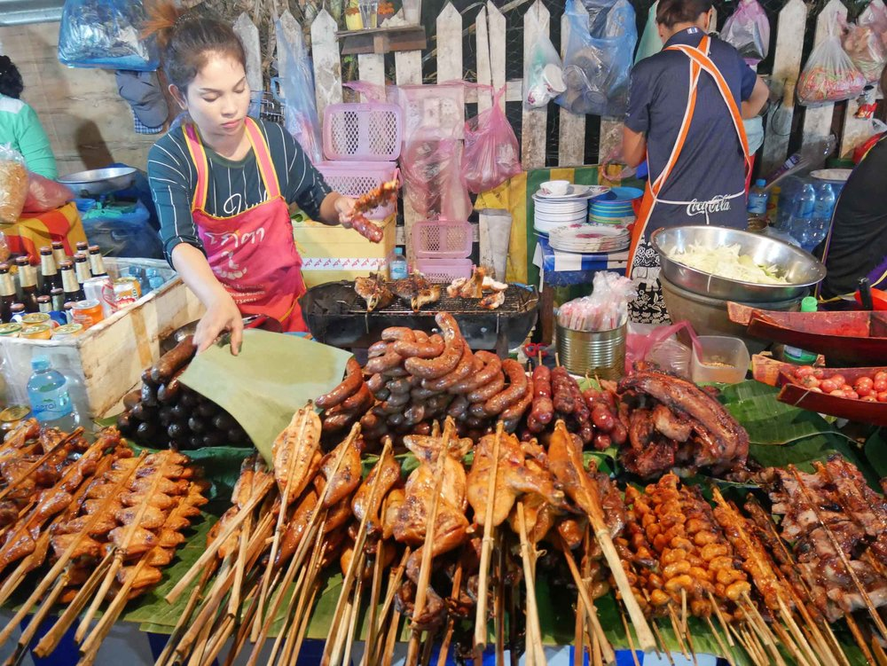 The night market's food district was smoky from the small grills that cooked various meats on long sticks.