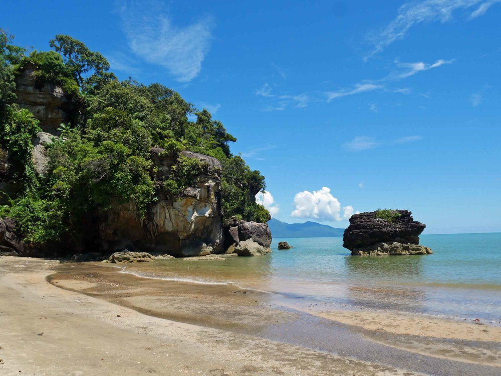 The trail ends at beautiful white sand beach with big rock formations carved by the sea.