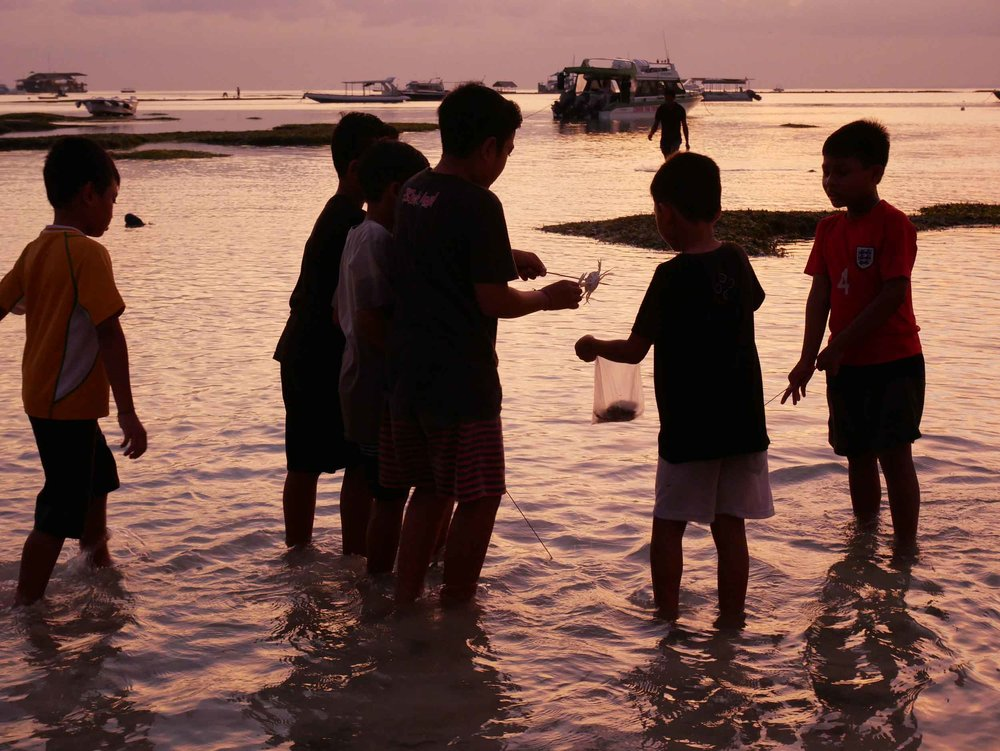 Young Balinese children playing and hunting for fish as we docked at sunset near Nusa Lembongan, Bali (May 14).
