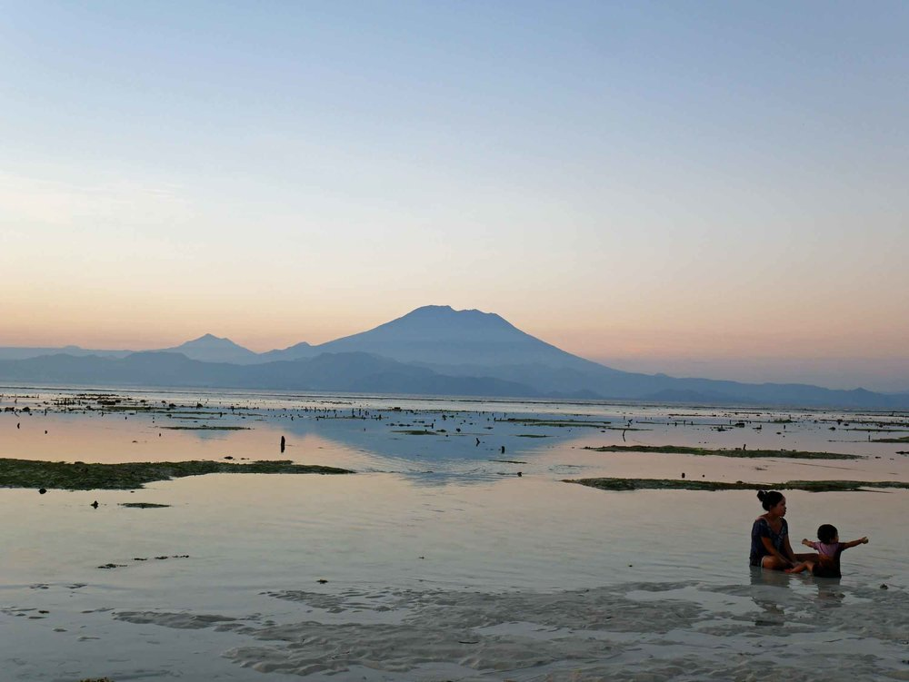 A pregnant Balinese mother plays with her daughter in the low tide of Pemedal Beach.