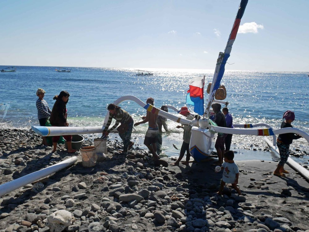 As the lateens approach shore, the crew and local villagers help push the boat onto rocky shore.