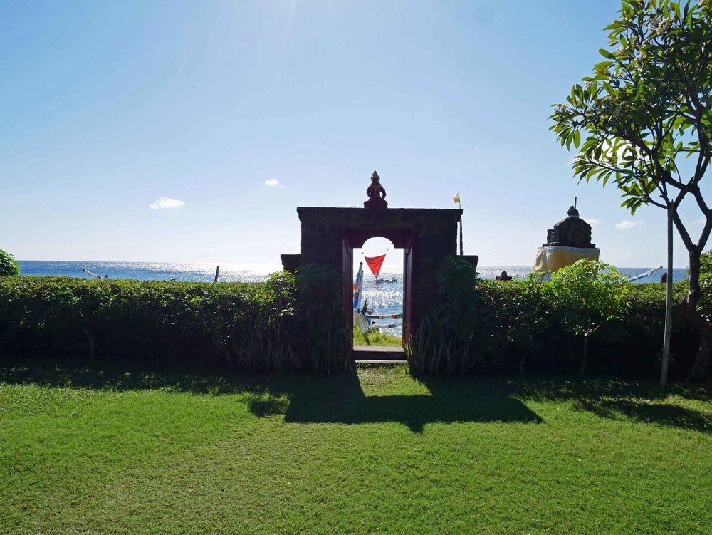 The verdant lawn and crimson gate of Meditasi leads to the black sand beach.