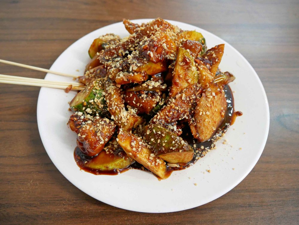 "First up,  rojak salad , which translates to ""mixture"" of raw fruit and vegetables in a thick dressing of tamarind, sugar, vinegar and salt and topped with sesame seeds."