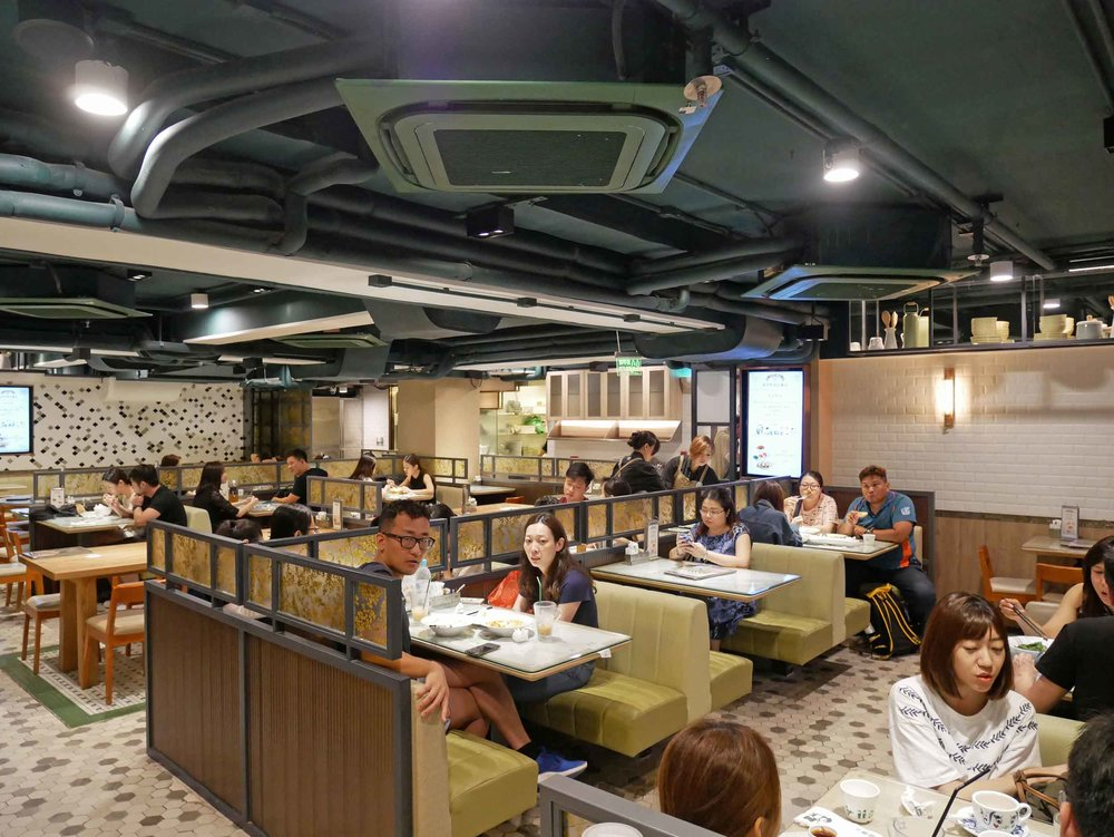 Patrons of Tsui Wah feasting on traditional Cantonese fare at this modern tea restaurant.