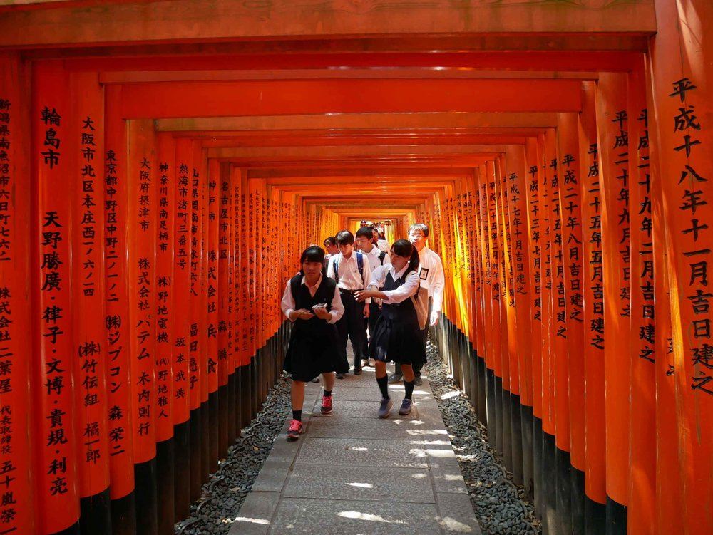 School kids running through the famed Inari gates and snapping pics as they go.