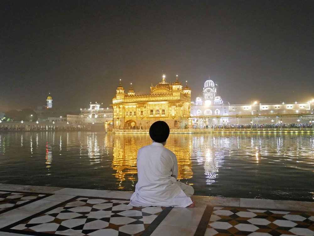 The Golden Temple, resplendent in its evening glow, seemingly floats atop the holy waters that surround the sacred inner-sanctum.