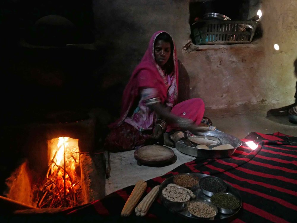 Our gracious host showing us how to prepare and bake  chapati  over her home's open fire.