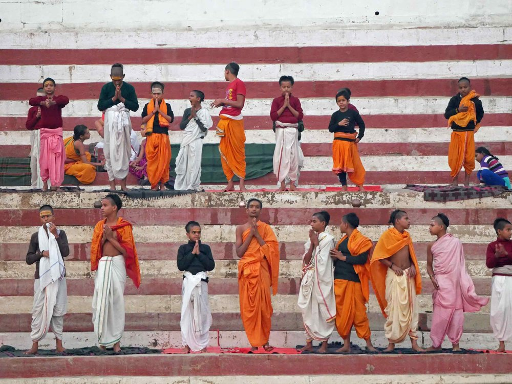 Young Hindu monks praying at the riverbank.