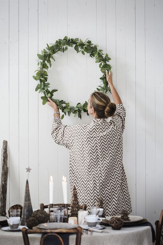 Jules and Louis Blog | festive wreaths - girl hanging wreath to wall
