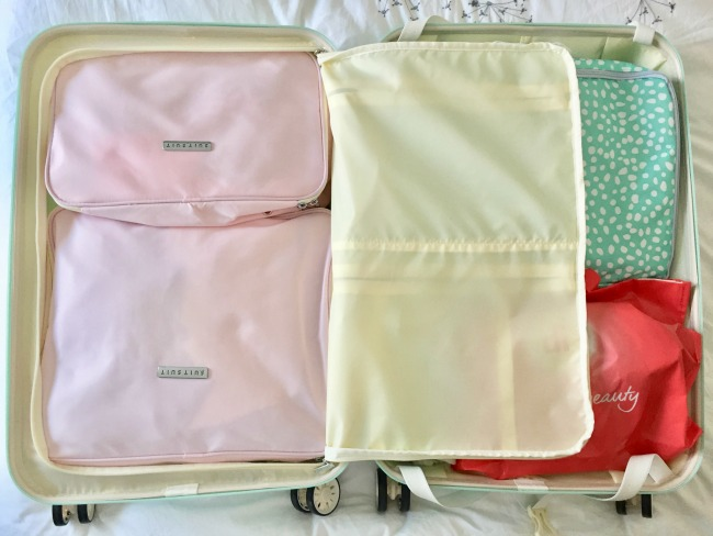 Jules and Louis Blog - How to pack for vacation - inside my suitcase Suit Suit - pink packing cubes.jpg