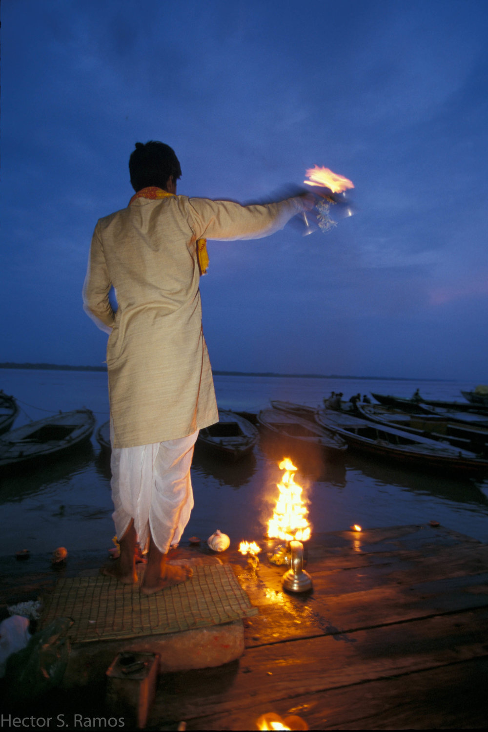 Evening aarti.  Varanasi.  During a monsoon there were not many people at the river Ganga. This pujari kept up with his daily ritual alone.  It was beautiful to witness - sincere devotion.  It brought deep stillness in me.  Photo: Nikon F5, 20-35mm f2.8, SB-28 flash, Provia 100.