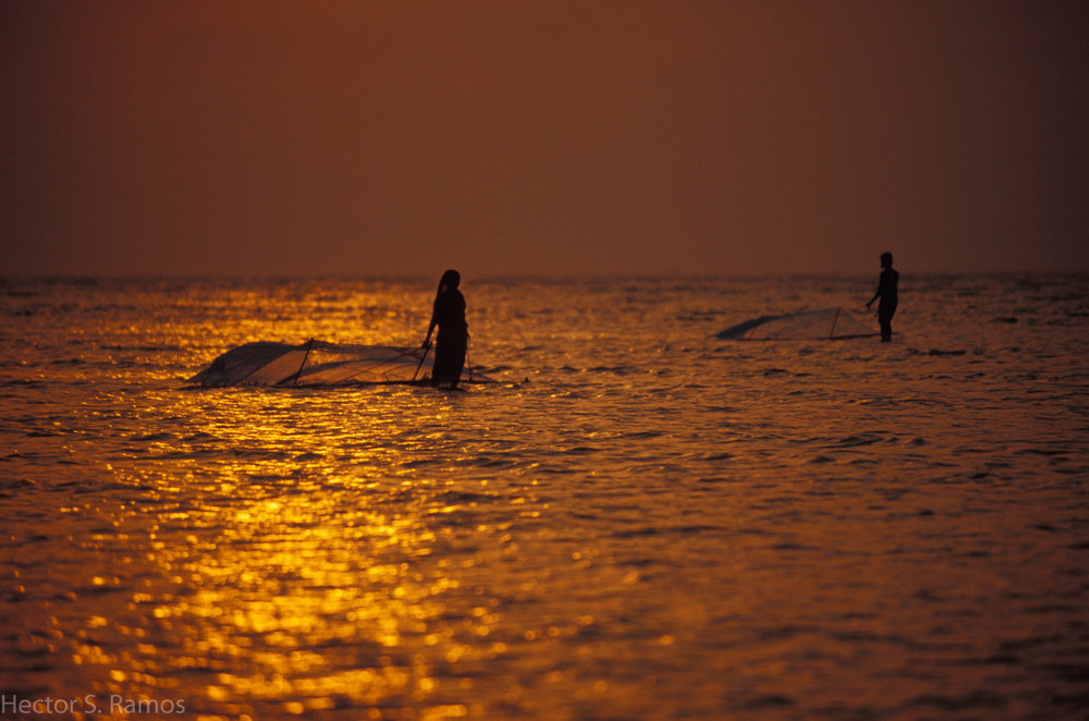 Fishing at sunrise.  Orissa.  I walked on a knee-deep calm water for several kilometers waiting for the sunrise.  My reward was being a witness to this couple.  Photo:  Nikon F5, AFD 80-200mm f2.8, Provia 100.