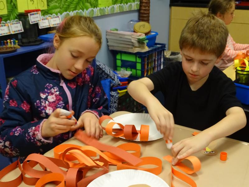 5th grader Adrienne Desrochers spent Community Service Day working with K-3rd graders on their four different projects. Here she is helping second grader Micah Killam make a turkey decoration for the trays of meals that were delivered to area residents at Thanksgiving.