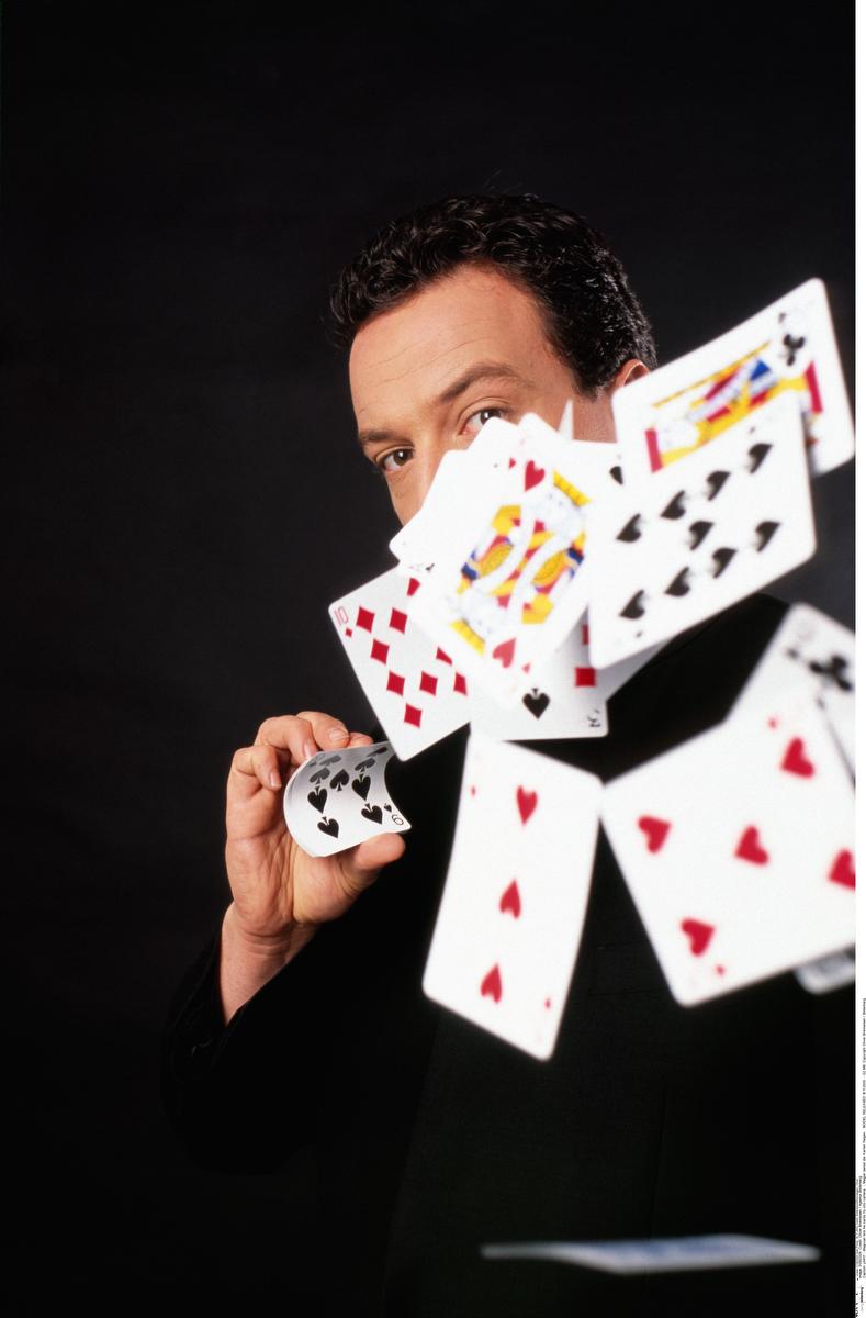 y9417 - Magician lets his cards fly into camera.- Magier laesst die Karten fliegen. MODEL RELEASED18.11.2005- 52 MB.Copyright Oliver Brenneisen