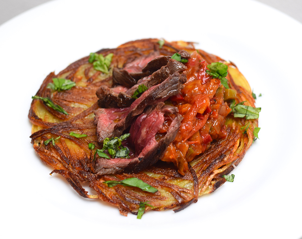 Steak and hash brown with sweet pepper and roasted tomato condiment and fresh coriander