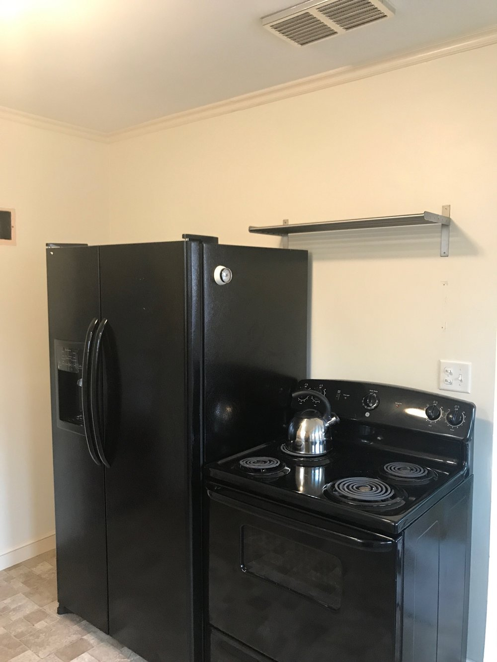 We had the refrigerator against the side wall and an IKEA metal shelving system in between for more storage. We also installed two metal shelves over the range when we moved in for additional storage (not pretty but it was functional).