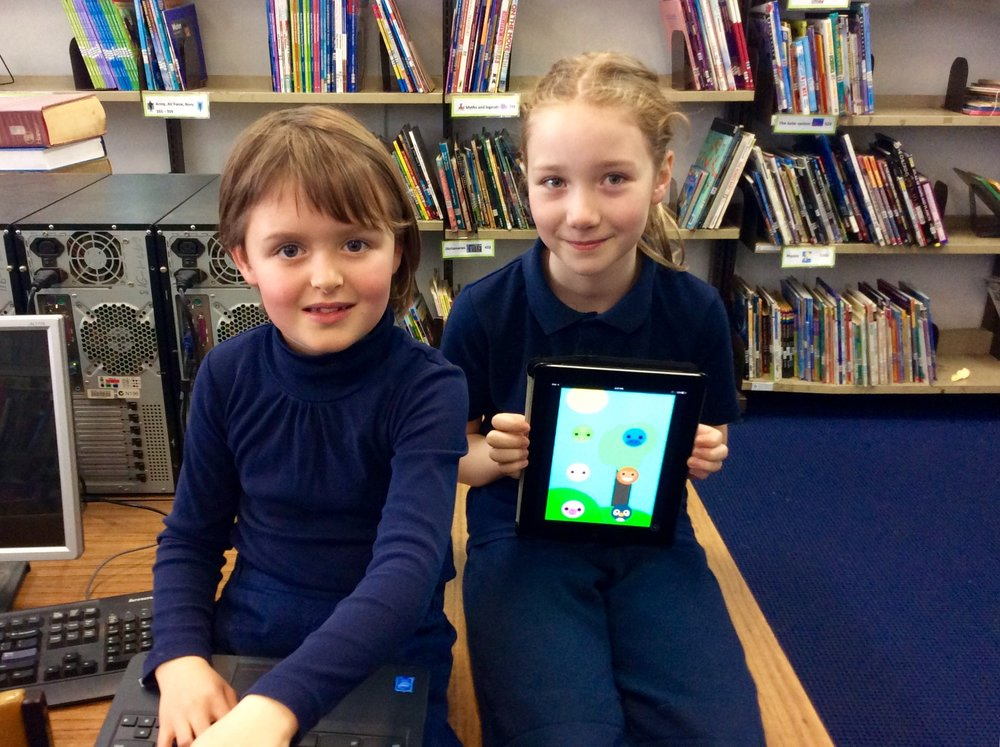 Nell & Poppy showing the app they made which is available on the Apple App Store.