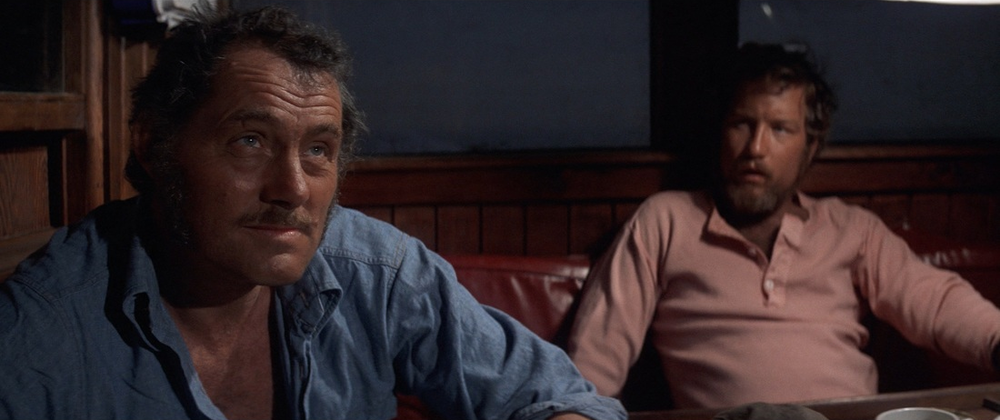 Quint (Robert Shaw) shares his story of being on the USS Indianapolis. Hooper (Richard Dreyfuss) looks on.