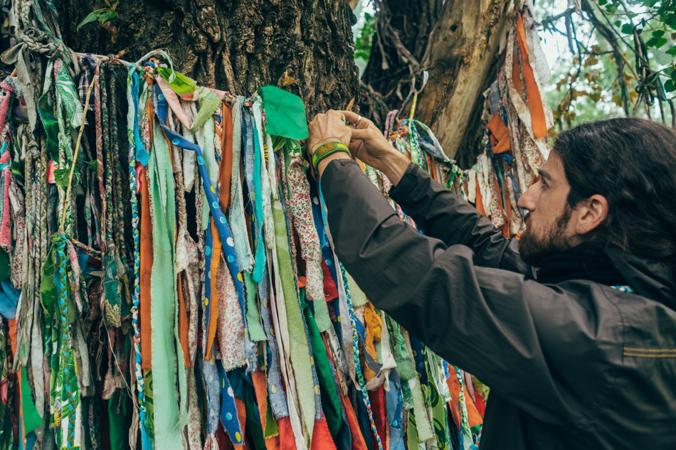 Emre puts ribbons on the holy tree. Each ribbon has a wish.