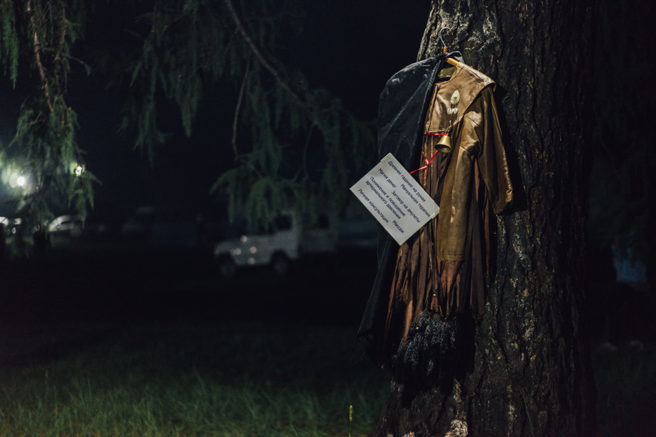 """Ljudmila's shaman dress hangs on the tree to attract potential customers. The sign says: """"Ancient fortune telling on stones.Manual therapy. Magic of money. Putting a spell on amulets. Reducing and rising of the blood pressure. Massage. Private consultation."""""""