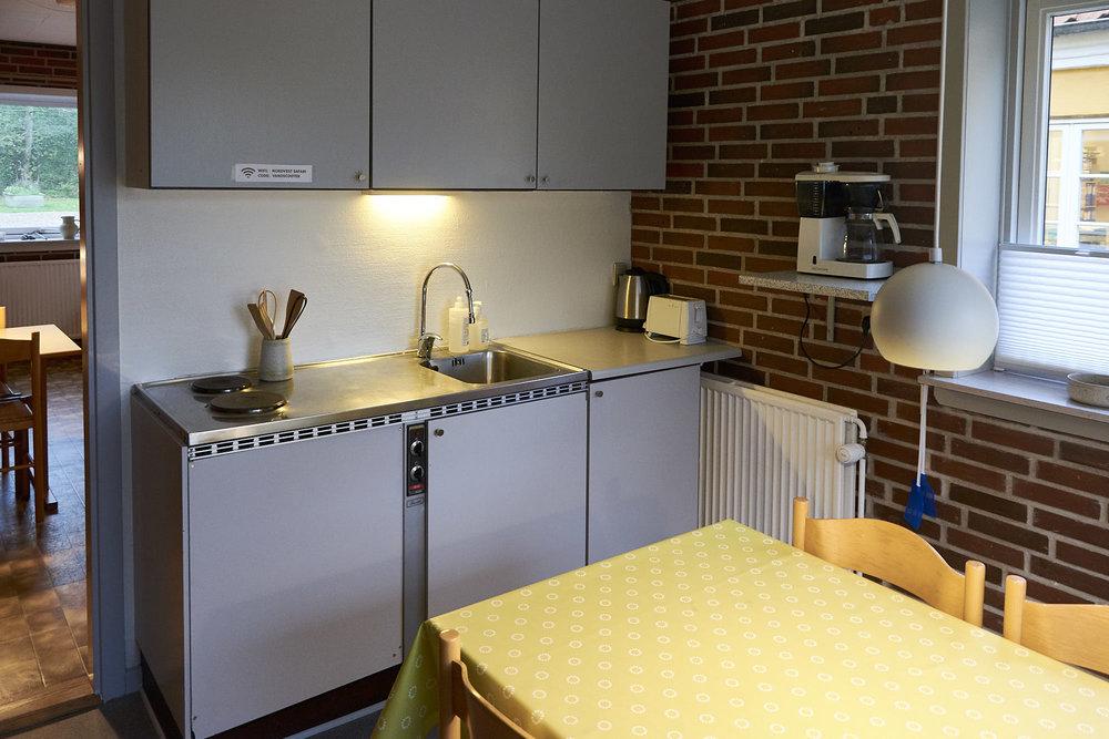 Lille køkken med to kogeplader, køleskab, mikrobølgeovn og kaffemaskine