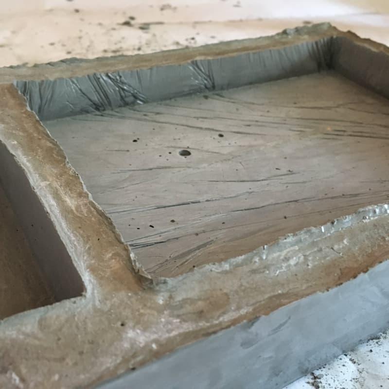 - Как видите, цемент очень хорошо повторяет рельеф поверхности той формы, которую вы используете. На поверхности большого отсека видны складки пищевой пленки, а на поверхности меньшего отсека - швы упаковки от кокосового молока.На одной из фото ниже видна разница в цвете и фактуре в местах, где смесь соприкасалась с картоном и где соприкасалась с гладким скотчем.