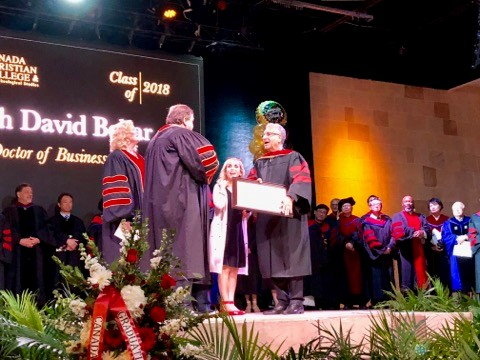 Yosi accepting his degree.