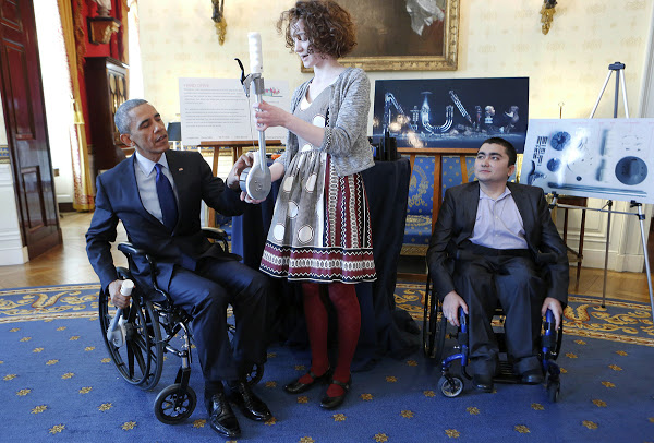 Reed demonstrating the 3D printableHand Drive Wheelchair Attachmentto PresidentBarack Obama.