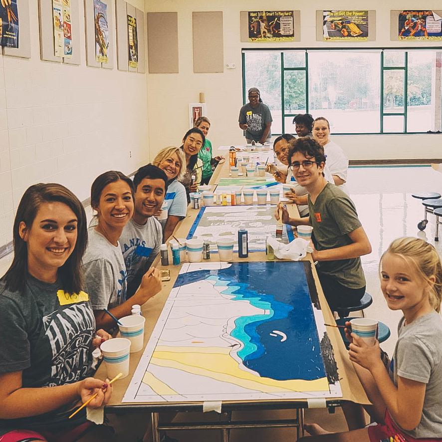 Volunteers at Hickman Elementary School paint a mural.