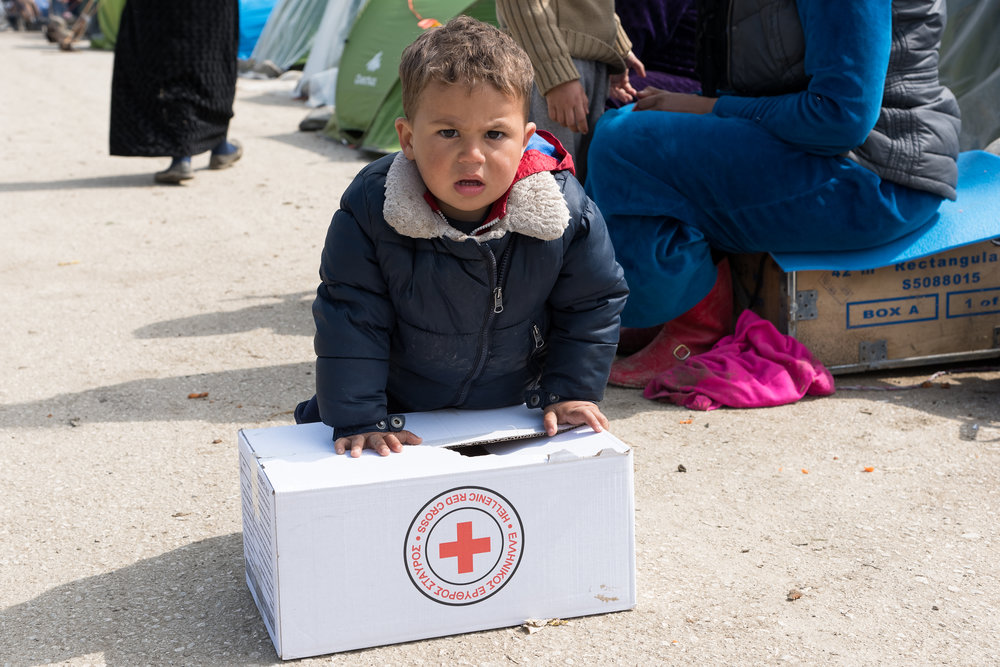 Eidomeni, Greece - March 17, 2016: A little boy tries to carry a box with supplies given from the Greek Red Cross on March 17, 2015 in the refugees camp of Eidomeni.
