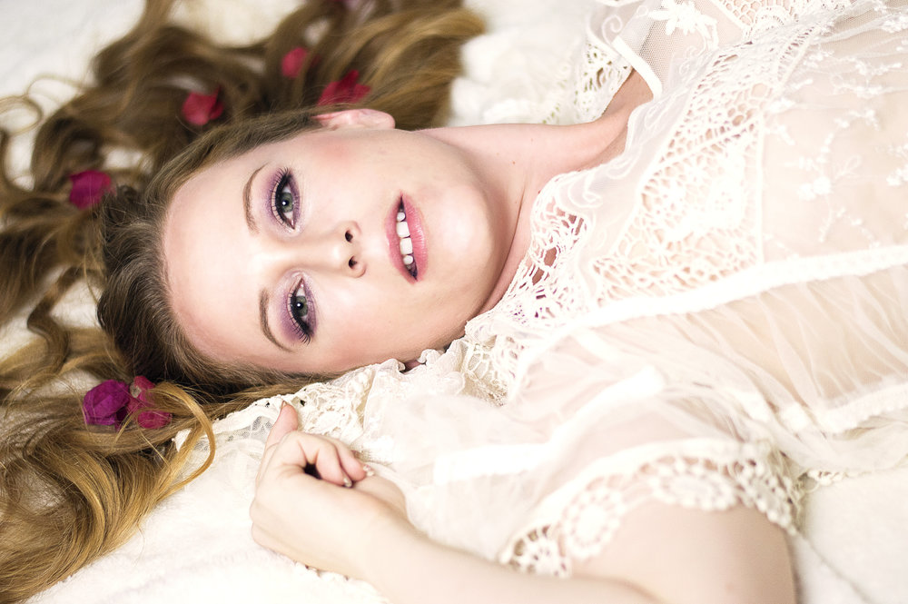 Boudoir photo with flower peddles on bed taken at The Bella Jade Collection Boudoir Photography in Phoenix Scottsdael, AZ