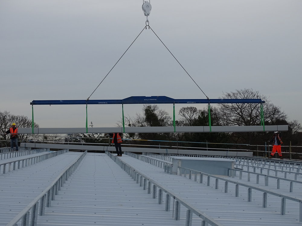 Contract crane lift of the Omnis Exteriors SpeedDeck profile standing-seam topsheets onto roof area